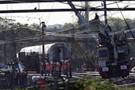 Track workers and officials work at the site of a derailed Amtrak train in Philadelphia, Pennsylvania, May 14, 2015. Seven people died and more than 200 were injured in the accident on Tuesday night when the train went barreling into a curved stretch of track at 100-plus miles per hour, twice the speed limit, when the engineer slammed on the brakes, U.S. investigators said on Wednesday. REUTERS/Mike Segar