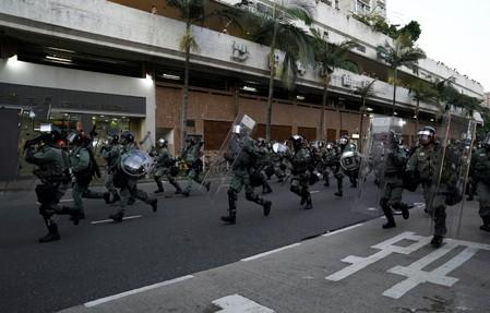 Police officers run during a demonstration by anti-government protesters in Sha Tin