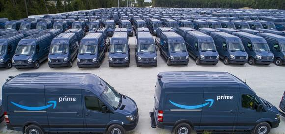 Dozens of dark-colored vans in a parking lot, all sporting the Amazon Prime logo.