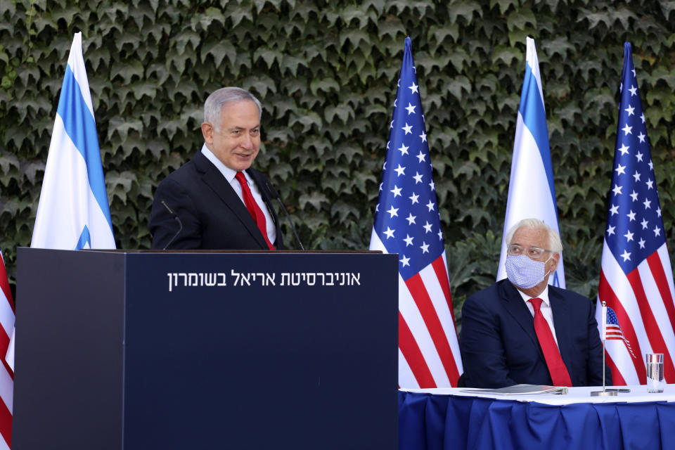 Israeli Prime Minister Benjamin Netanyahu, left, speaks during a ceremony to sign amendments to a series of scientific cooperation agreements with U.S. Ambassador to Israel David Friedman, at Ariel University, in the West Bank settlement of Ariel, Wednesday, Oct. 28, 2020. The United States and Israel amended the agreements on Wednesday to include Israeli institutions in the West Bank, a step that further blurs the status of settlements widely considered illegal under international law. (Emil Salman/Pool via AP)