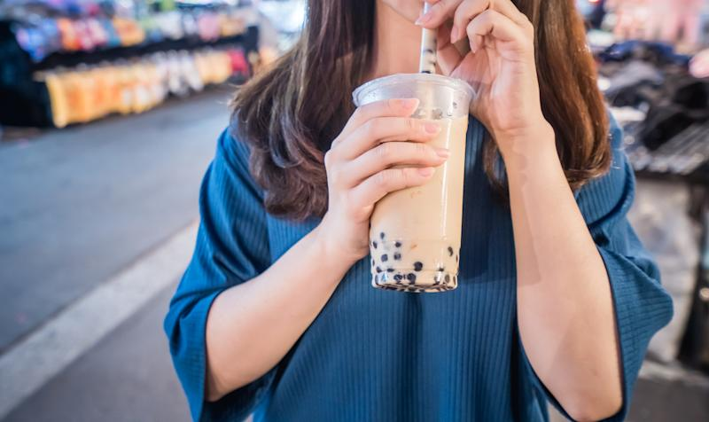 A young woman is drinking a plastic cup of bubble milk tea with a straw at a night market in Taiwan. (PHOTO: Getty Images)