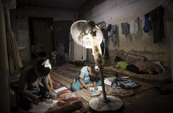 Palestinian children do their homeworks during a power cut in an impoverished area in Gaza City, on September 11, 2017, the result of a dispute between the Palestinian Authority and Hamas (AFP Photo/MAHMUD HAMS)