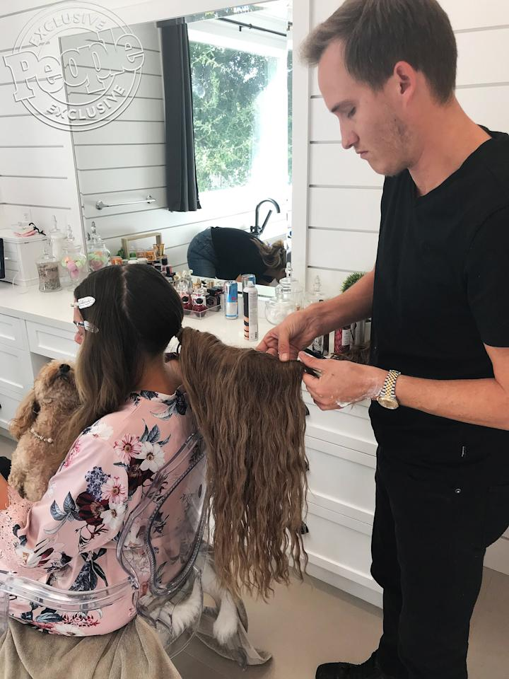"""""""We went for a natural wave which is a bit different than her typical beach or glam wave,"""" says Leake. """"I wanted the vibe to feel effortless yet fashion-forward so we added some major length using <a href=""""http://hiddencrownhair.com"""">HiddenCrownHair</a> Clip In Extensions (color #612) to give her a major ponytail.""""  He achieved those natural waves by spraying generous amounts of <a href=""""https://www.colorwowhair.com/us/dream-coat-curly-cw530.html"""">ColorwowDreamcoat Curly</a>, a super light-weight styling spray that delivers shiny, defined """"crunch-free"""" curls."""