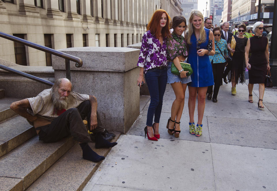 Fashionistas pose for photographs in front of a homeless man outside Moynihan Station following a showing of the Rag & Bone Spring/Summer 2013 collection during New York Fashion Week September 7, 2012. (Photo: REUTERS/Lucas Jackson)