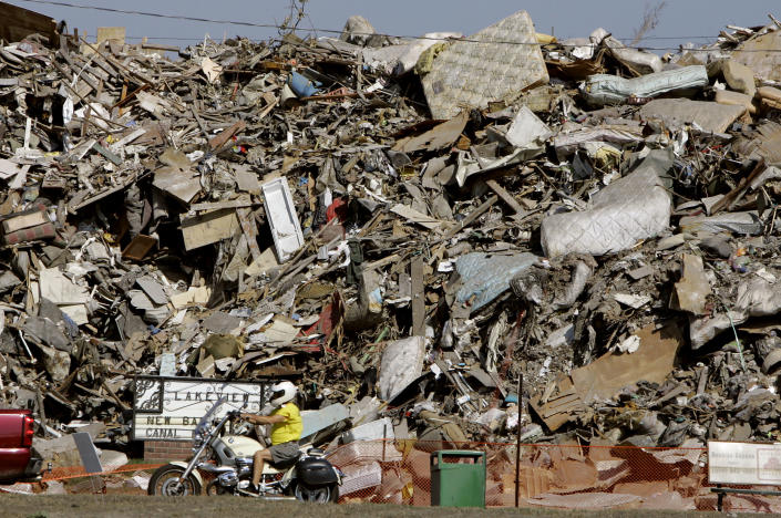 "FILE - In this Oct. 22, 2005 file photo, a motorcyclist rides past a mountain of trash, sheet rock and domestic furniture, removed from homes damaged by Hurricane Katrina, at one of three dump areas setup for that purpose, in New Orleans, LA. In the cases of the big storms like Haiyan, Sandy and Hurricane Katrina in 2005, the poor were the most vulnerable, a United Nations scientific panel reports said. The report talks about climate change helping create new pockets of poverty and ""hotspots of hunger"" even in richer countries, increasing inequality between rich and poor. (AP Photo/Nati Harnik, File)"