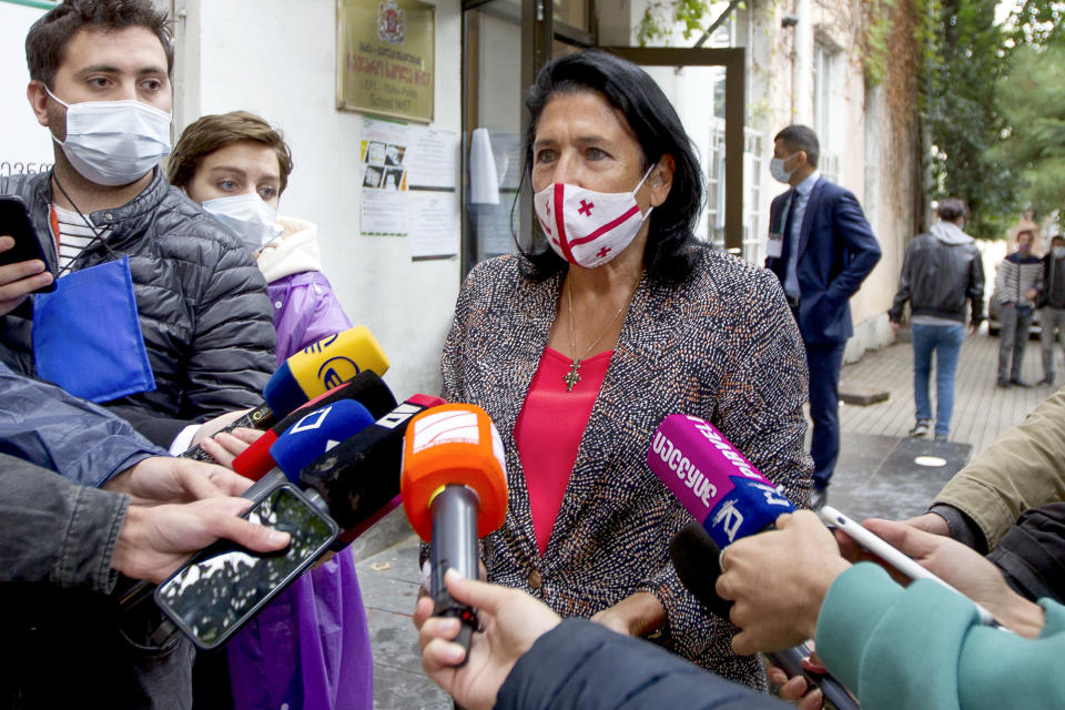 Georgia's President Salome Zurabishvili, center, wearing a face mask to help curb the spread of the coronavirus, speaks to journalists at a polling station during national municipal elections in Tbilisi, Georgia, Saturday, Oct. 2, 2021. Former President Mikheil Saakashvili was arrested after returning to Georgia, the government said Friday, a move that came as the ex-leader sought to mobilize supporters ahead of the national municipal elections seen as critical to the country's political makeup. The elections started Saturday. (AP Photo/Shakh Aivazov)
