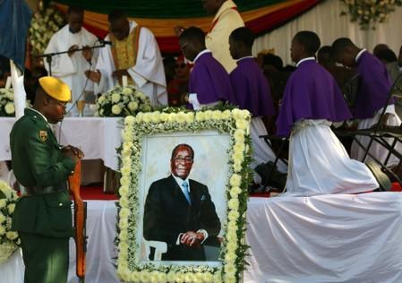 Soldiers stand beside a picture of former Zimbabwean President Robert Mugabe during a church service before his burial at his rural village in Kutama
