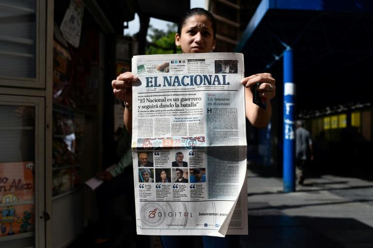 """A woman holds up the final printed edition of El Nacional on December 14, 2018, with its front page reading """"El Nacional is a warrior and will keep on fighting"""""""