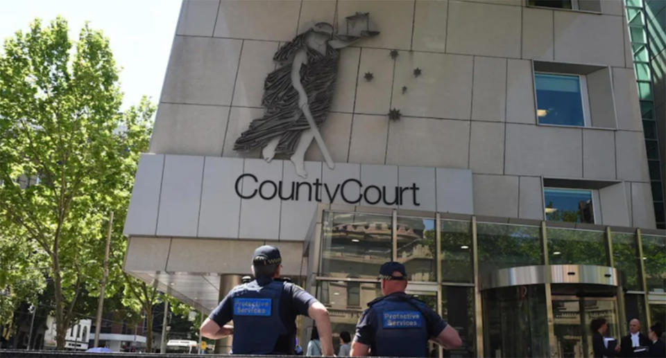 Police officers walk into Victoria County Court.