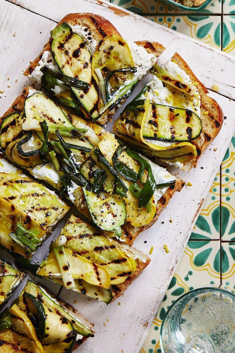 """<p>Transform basic garlic bread into this deliciously light meal with ricotta, garlic, and grilled veggies.</p><p><em><a href=""""https://www.womansday.com/food-recipes/food-drinks/a22469348/grilled-squash-garlic-bread-recipe/"""" rel=""""nofollow noopener"""" target=""""_blank"""" data-ylk=""""slk:Get the Grilled Squash Garlic Bread recipe."""" class=""""link rapid-noclick-resp"""">Get the Grilled Squash Garlic Bread recipe.</a></em></p>"""