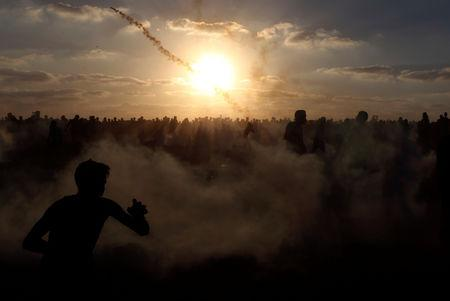 Palestinians run from tear gas during a protest calling for lifting the Israeli blockade on Gaza and demanding the right to return to their homeland at the Israel Gaza border fence in the southern Gaza Strip