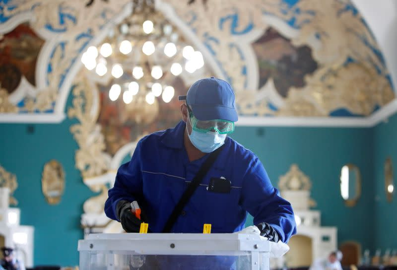 A specialist disinfects a ballot box during a nationwide vote on constitutional reforms in Moscow