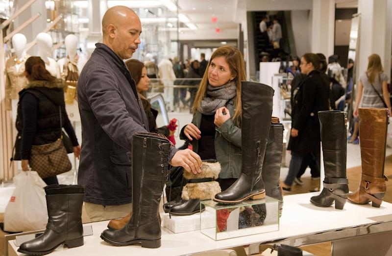 In this photo of Friday, Oct. 12, 2012, customers shop for Rudsak shoes at Macy's shoe department in New York. Shoes are coming out of the closet and landing under the Christmas tree. They're a top seller this holiday season _ a big feat considering they don't usually make peoples' gift lists. (AP Photo/Mark Lennihan)