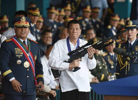 Philippine President Rodrigo Duterte holds a Galil sniper rifle next to outgoing Philippine National Police Chief Ronald Bato Dela Rosa during the National Police chief handover ceremony in Camp Crame, Quezon City, metro Manila, Philippines, April 19, 2018. REUTERS/Dondi Tawatao