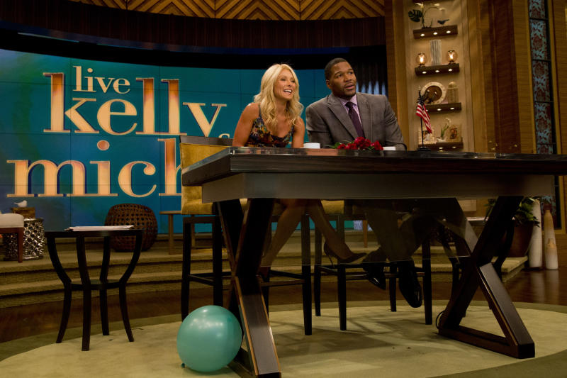 """Former football player Michael Strahan, right, sits with Kelly Ripa on the set of the newly named """"Live! with Kelly and Michael"""" on Tuesday, Sept. 4, 2012 in New York. Strahan joined the popular morning show as a permanent co-host on Tuesday, fulfilling a joking prophecy he made to Regis Philbin more than four years ago. The gap-toothed former New York Giant jogged onto the morning show set and picked up co-host Kelly Ripa in a bear hug, lifting her off her feet. He replaces Philbin, who left last November. Strahan was the survivor in a series of on-air tryouts of potential co-hosts since Philbin left, and his hiring has been an open secret for the past two weeks. (Photo by Charles Sykes/Invision/AP Images)"""
