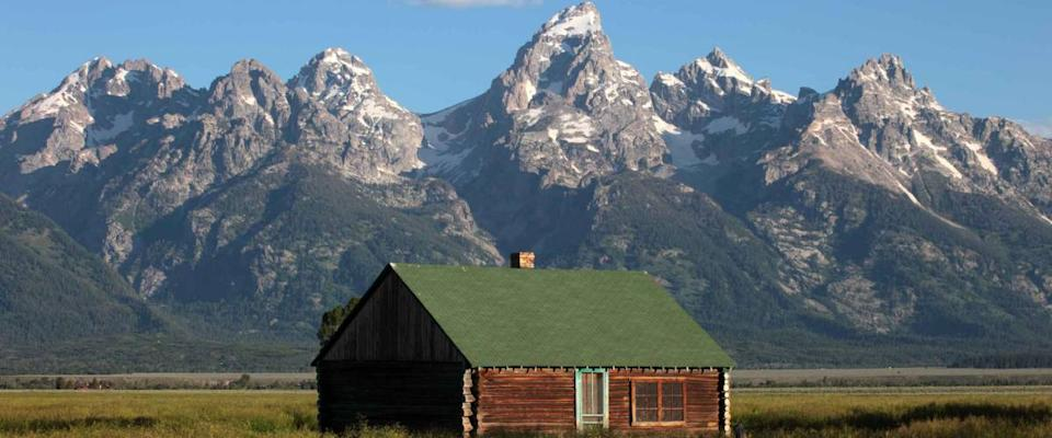 A weathered home sits against the backdrop of the Grand Tetons in Wyoming