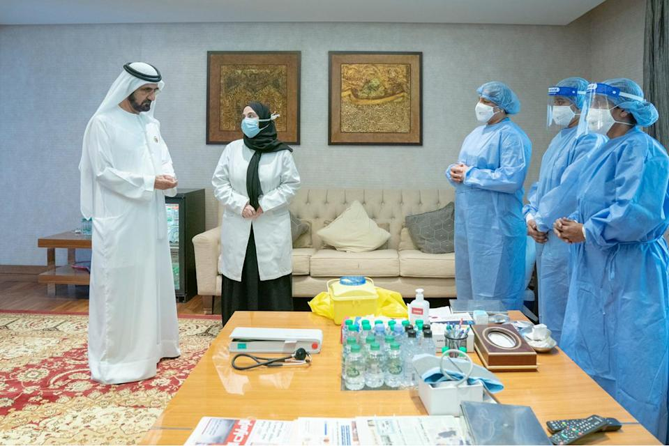 Prime Minister and Vice-President of the United Arab Emirates and ruler of Dubai Sheikh Mohammed bin Rashid al-Maktoum talks to staff before he receives the coronavirus disease (COVID-19) vaccine candidate, in Dubai, United Arab Emirates November 3, 2020. WAM/Handout via REUTERS. ATTENTION EDITORS - THIS IMAGE WAS PROVIDED BY A THIRD PARTY.