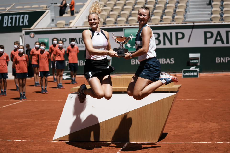 Czech Republic's Barbora Krejcikova, right, and compatriot Katerina Siniakova jump while holding the cup after defeating USA's Bethanie Mattek-Sands and Poland's Iga Swiatek in their women's doubles final match of the French Open tennis tournament at the Roland Garros stadium Sunday, June 13, 2021 in Paris. (AP Photo/Thibault Camus)