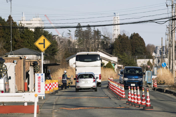 A security guard stops vehicles at a security checkpoint as they enter an area that requires a special permit to enter in Okuma town, Fukushima prefecture, northeastern Japan, Thursday, Feb. 25, 2021. Part of the buildings at the Fukushima Daiichi nuclear power plant is seen in the background. (AP Photo/Hiro Komae)