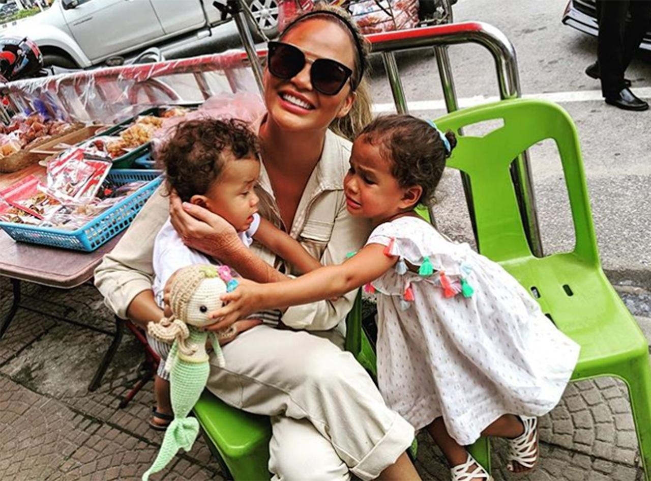 """Chrissy Teigen and John Legend's summer trip to Thailand looked picture perfect — for the most part. From beachy photo shoots and island-hopping to matching henna tattoos, the power couple and their adorable mini-mes, daughter Luna, 3, and son Miles, 15 months, had us hoping they'll adopt us in time for their next family getaway.  But Teigen isn't one to shy away from a <a href=""""https://people.com/parents/chrissy-teigen-shares-candid-photo-luna-miles-crying/"""">candid photo</a>, and she took the opportunity to remind her followers about what it's really like to travel with two young kids in tow.  """"Everything's fine over here,"""" she hilariously captioned <a href=""""https://www.instagram.com/p/B1pVQXvBfg-/"""">a snap</a> of herself smiling as a distraught Luna and Miles looked to be fighting over a mermaid toy across her lap."""