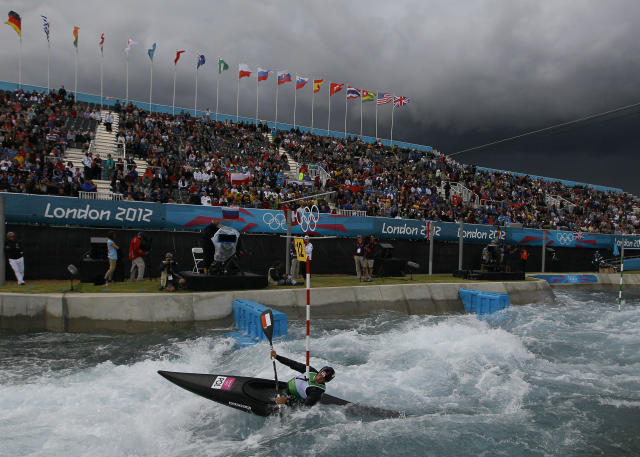 The sky turns black before a heavy rain shower as Poland's Mateusz Polaczyk competes in the heats of the K-1 men's canoe slalom at Lee Valley Whitewater Center, at the 2012 Summer Olympics, Sunday, July 29, 2012, in London. (AP Photo/Kirsty Wigglesworth)