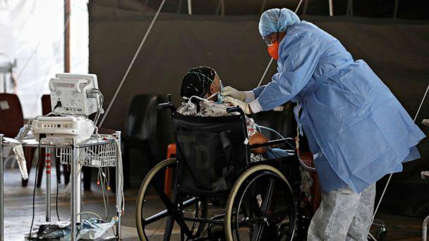 PHOTO: Healthcare workers tend to a patient at a temporary ward set up during the COVID-19 outbreak at Steve Biko Academic Hospital in Pretoria, South Africa, Jan. 19, 2021. (Pool/Reuters)