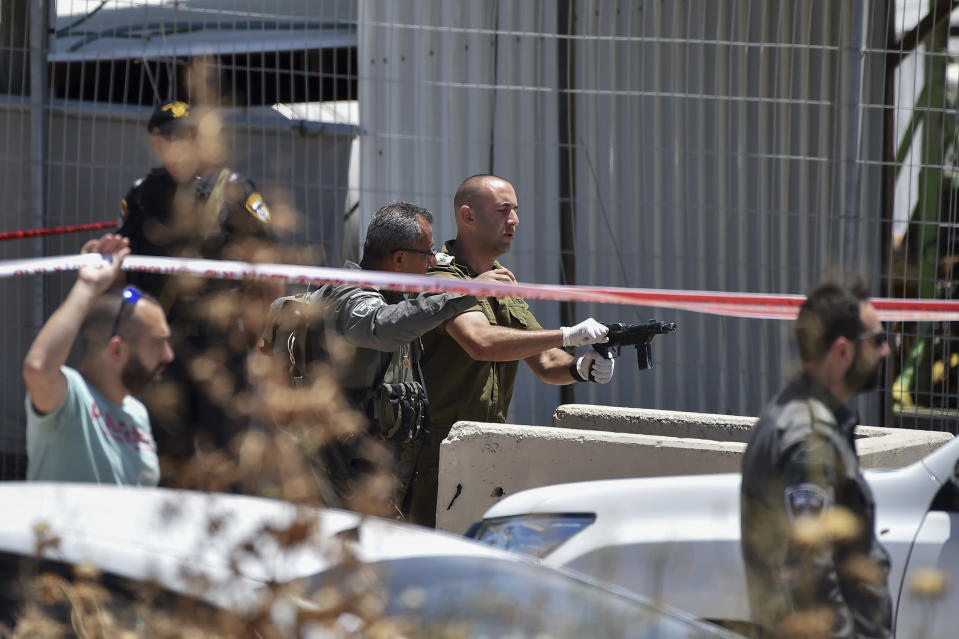 An IDF officer inspects the weapon used by a Palestinian gunmen at the scene of shooting attack in front of the military base of Salem near the West Bank town of Jenin, Friday, May. 7, 2021. Israeli troops shot and killed two Palestinians and wounded a third after the men opened fire on a Border Police base in the occupied West Bank. It was the latest in a series of violent confrontations amid soaring tensions in Jerusalem. (AP Photo/Gil Eliyahu)