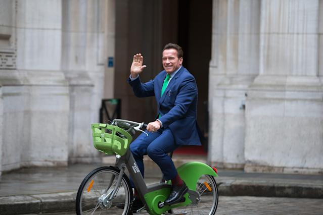 Arnold Schwarzenegger waves as he rides a bicycle in Paris on December 11, 2017. (Michel Stoupak/NurPhoto via Getty Images)