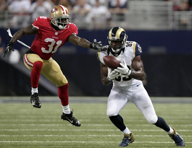 St. Louis Rams tight end Jared Cook, right, catches a pass for an 18-yard gain after it was tipped by San Francisco 49ers safety Donte Whitner, left, during the second quarter of an NFL football game Thursday, Sept. 26, 2013, in St. Louis. (AP Photo/Tom Gannam)