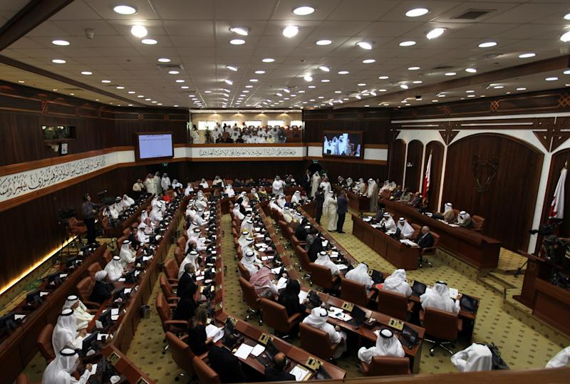 Bahraini lawmakers participate in a special session of parliament to discuss how to handle the uprising in the Gulf island kingdom, convened in Manama, Bahrain, Sunday, July 28, 2013. Several members of Bahrain's parliament, which doesn't include opposition groups, called for harsher methods against protesters, including stripping citizenship, establishing curfews, instituting martial law, employing the death penalty and banning all protests. (AP Photo/Hasan Jamali)