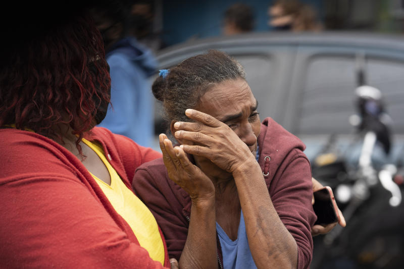 A woman is comforted as she reacts to seeing several bodies covered with linens after an armed confrontation in the Alemao slum complex in Rio de Janeiro, Brazil, Friday, May 15, 2020. According to the civil police, 10 people were found dead during the police operation against alleged drug traffickers. (AP Photo/Leo Correa)