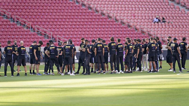 Players and staff gather on the field before the scheduled game between Real Salt Lake and LAFC.