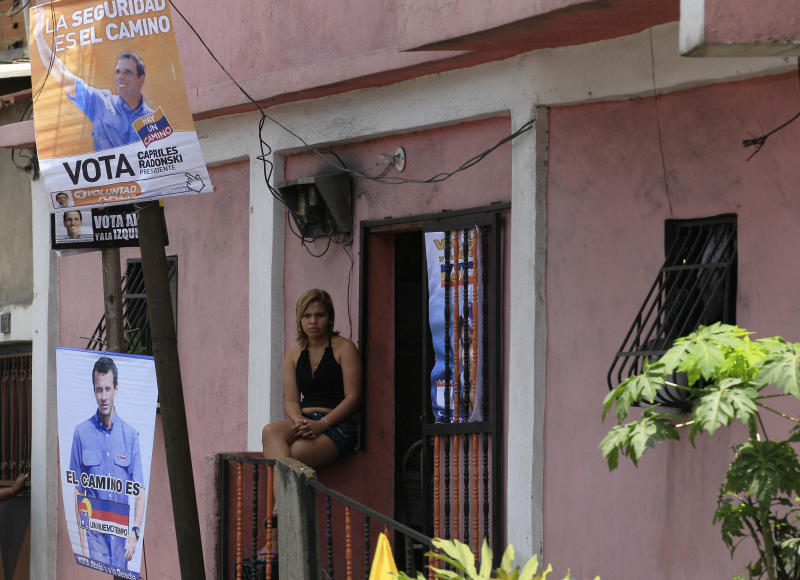 In this Sept. 16, 2012 photo, a woman sits outside of her home decorated with campaign posters of opposition presidential candidate Henrique Capriles in the shantytown of Petare in Caracas, Venezuela. From single mothers to construction workers, a segment of President Hugo Chavez supporters have been turning away from the president and instead considering new leadership. They've become key to the Oct. 7 presidential vote and Capriles' strategy. (AP Photo/Fernando Llano)