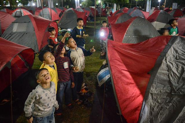 <p>Indonesian children look at the blood moon while waiting for a lunar eclipse at Salman Astro Camp in Bandung, Indonesia, July 28, 2018. (Photo: Antara Foto/Raisan Al Farisi via Reuters) </p>