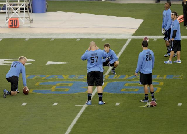 Members of the UCLA team stop at an on-field memorial for UCLA wide receiver Nick Pasquale before an NCAA college football game against New Mexico State, Saturday, Sept. 21, 2013 in Pasadena, Calif. Pasquale was struck and killed by a car Sept. 8, in San Clemente, Calif. (AP Photo/Chris Carlson)
