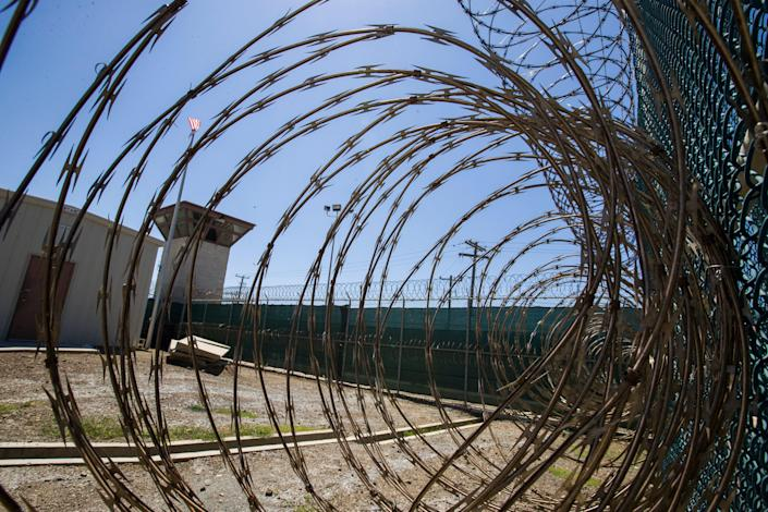 <p>In this Wednesday, April 17, 2019 file photo reviewed by U.S. military officials, the control tower is seen through the razor wire inside the Camp VI detention facility in Guantanamo Bay Naval Base, Cuba.</p> ( (AP Photo/Alex Brandon, File))