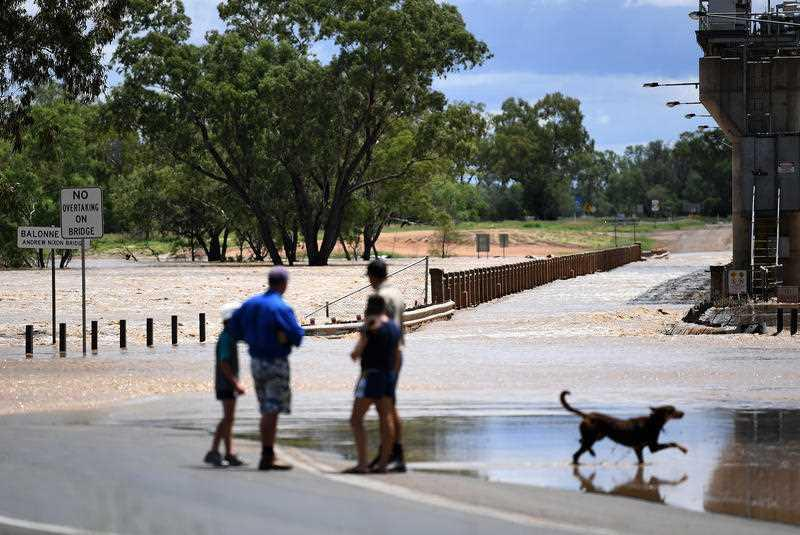 Local watch as the swollen Balonne river floods the Andrew Nixon bridge in St George, south-western Queensland.