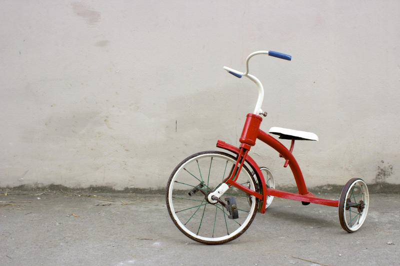 Red Antique Children's Tricycle in front of a Grey Wall.