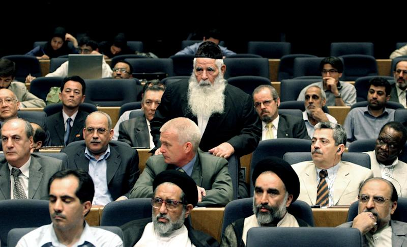 FILE - In this Tuesday, Aug. 1, 2006 file photo, Iran's Jewish community chief rabbi, Yousef Hamedani Cohen, center, arrives at a conference of Iranian parties to show support for Palestinians and Lebanon, in Tehran, Iran. Cohen, Iran's former chief rabbi and one of the cornerstones of its tiny Jewish community, has died. He was 98. (AP Photo/Vahid Salemi, File)