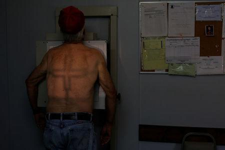 Retired coal miner James Marcum, who has complicated black lung disease, stands for a chest x-ray at the Stone Mountain Health Services in St. Charles, Virginia, U.S., May 18, 2018. Marcum worked at a surface strip mine for 20-25 years, but has not yet been approved for benefits for his black lung disease. REUTERS/Brian Snyder