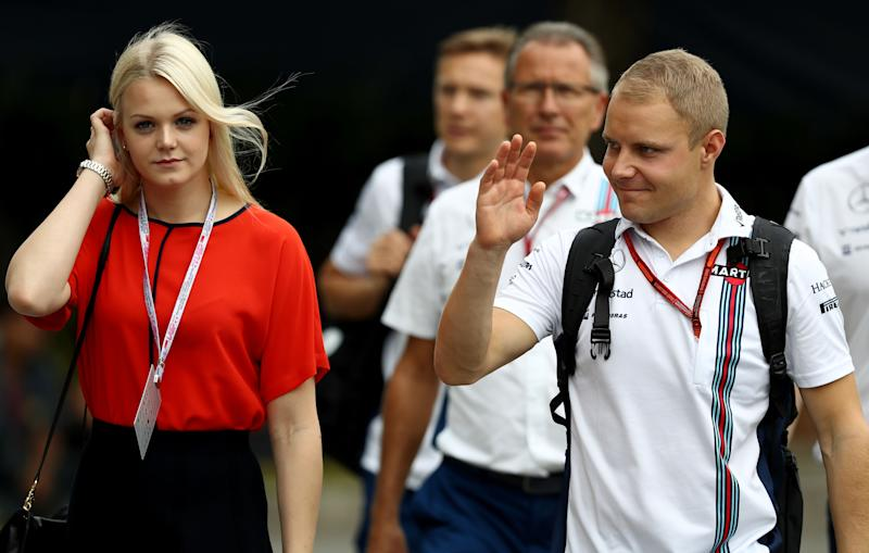 SINGAPORE - SEPTEMBER 17: Valtteri Bottas of Finland and Williams walks into the paddock with wife Emilia Pikkarainen before final practice for the Formula One Grand Prix of Singapore at Marina Bay Street Circuit on September 17, 2016 in Singapore. (Photo by Lars Baron/Getty Images)