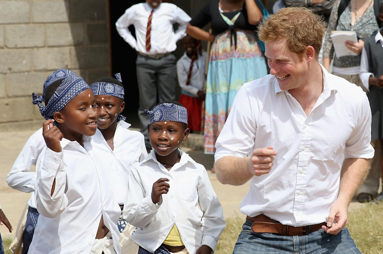 MASERU, LESOTHO - FEBRUARY 27:  Prince Harry dances with deaf children during at visit to the Kananelo Centre for the deaf, a project supported by his charity Sentebale on February 27, 2013 in Maseru, Lesotho. Sentebale is a charity founded by Prince Harry and Prince Seeiso of Lesotho. It helps the most vulnerable children in Lesotho get the support they need to lead healthy and productive lives. Sentebale works with local grassroots organisations to help these children, the victims of extreme poverty and Lesotho's HIV/AIDS epidemic. Cathy Ferrier was appointed as Sentebale's Chief Executive in March 2012 and is spearheading a fundraising initiative to build the Mamohato Centre which will provide psychosocial support for children and young people infected with HIV. Prince Harry is due to pay a visit to Lesotho this week to catch up on his charity's progress and meet key children who will be supported by the charity.  (Photo by Chris Jackson/Getty Images)