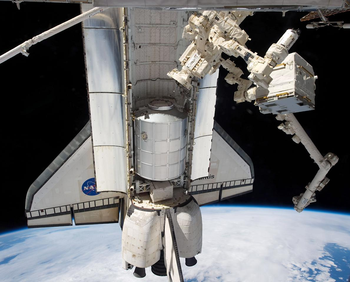 IN SPACE - JULY 18:  In this handout image provided by the National Aeronautics and Space Administration (NASA), NASA space shuttle Atlantis' cargo bay holds the Raffaello multi-purpose logistics module seen from the International Space Station before the two spacecraft undocked July 18, 2011 in space. The object connected to the station at right in the grasp of Dextre, a robot hand, is the Cargo Transport Container-2 (CTC-2) which was delivered by JAXA's HTV-2 vehicle earlier in the year. Space shuttle Atlantis is on the last leg of a 12-day mission to the International Space Station where it delivered the Raffaello multi-purpose logistics module packed with supplies and spare parts. This was the final mission of the space shuttle program, which began on April 12, 1981 with the launch of Colombia.  (Photo by NASA via Getty Images)