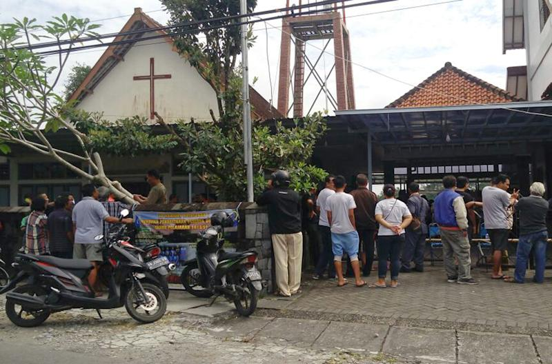 Onlookers gather outside of St. Lidwina Church following an attack in Sleman, Yogyakarta province, Indonesia,Sunday, Feb. 11, 2018. Police shot a sword-wielding man who attack the church during a mass, injuring a number of people. (AP Photo/Slamet Riyadi)