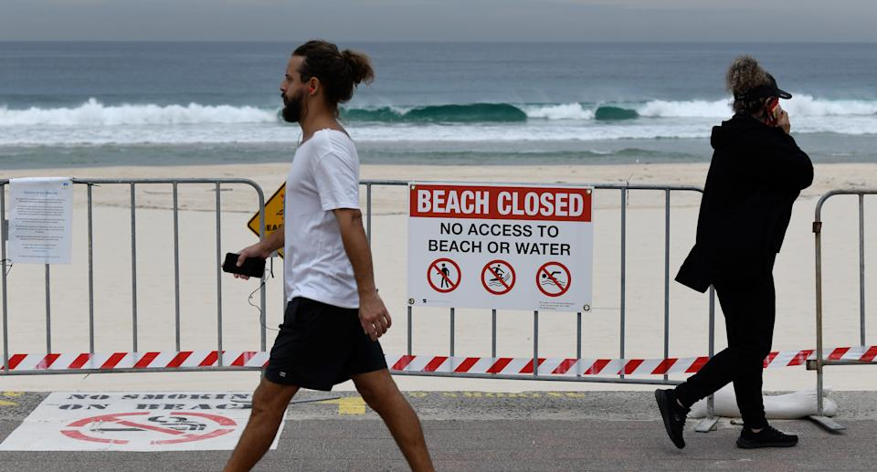 People are seen walking along Bondi Beach in Sydney past a 'beach closed' sign.