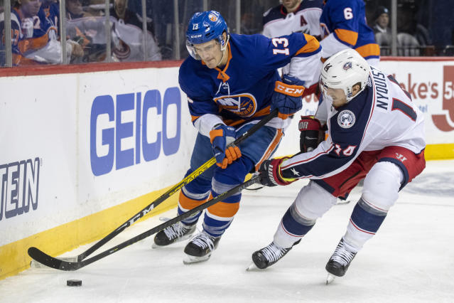 New York Islanders center Mathew Barzal (13) fights for the puck against Columbus Blue Jackets center Gustav Nyquist (14) during the first period of an NHL hockey game, Saturday, Nov. 30, 2019, in New York. (AP Photo/Mary Altaffer)