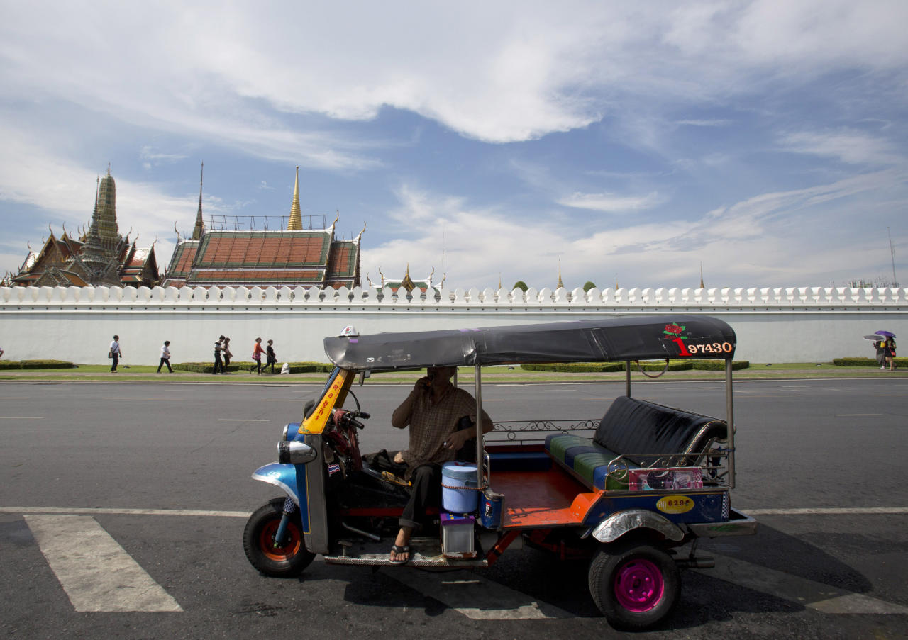 A motor tricycle driver, foreground, waits for customer as foreign tourists, background, walk near the wall of the Grand Palace during a tour Tuesday, May 27, 2014 in Bangkok, Thailand. For Thailand's tourist industry, the situation is more ominous. Bookings were already down after six months of anti-government protests in Bangkok, and the combination of coup plus curfew along with uncertainty over how long the crackdown will last could be bruising, hotels and industry experts say. It's a blow the economy, already struggling, could do without. (AP Photo/Sakchai Lalit)