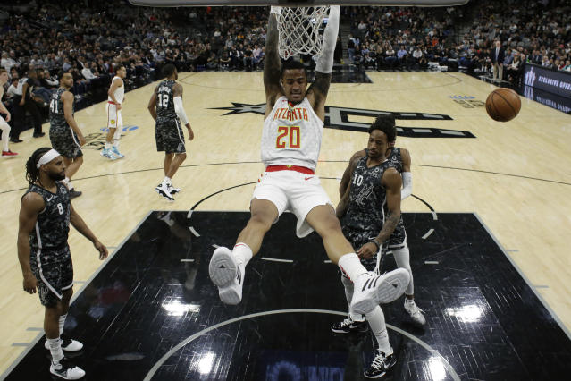 Atlanta Hawks forward John Collins (20) scores over San Antonio Spurs guard DeMar DeRozan (10) during the first half of an NBA basketball game in San Antonio, Friday, Jan. 17, 2020. (AP Photo/Eric Gay)