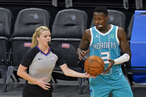 Referee Jenna Schroeder, left, hands the ball to Charlotte Hornets guard Terry Rozier (3) to put the ball in play during the first half of an NBA basketball game between the Orlando Magic and the Charlotte Hornets, Monday, Jan. 25, 2021, in Orlando, Fla. Natalie Sago and Jenna Schroeder made up two-thirds of the crew assigned to the Charlotte at Orlando game, the first time in NBA history that two women were assigned to work a regular-season contest together.(AP Photo/John Raoux)