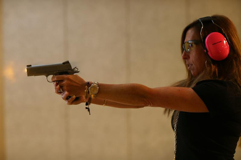 BOCA RATON, FL - OCTOBER 21: Susan Kushlin shoots a pistol while wearing one of the bracelets that her company, Gun Girls, Inc., created for women that enjoy guns on October 21, 2013 in Boca Raton, Florida. Her line includes bullet jewelry, handbags, belts and custom logo apparel with some of the items priced at $35 gold-toned bullet belts, $20 dangling gun earrings, $76 pink concealed-carry handbags and $21 rhinestone-studded tank tops. (Photo by Joe Raedle/Getty Images)